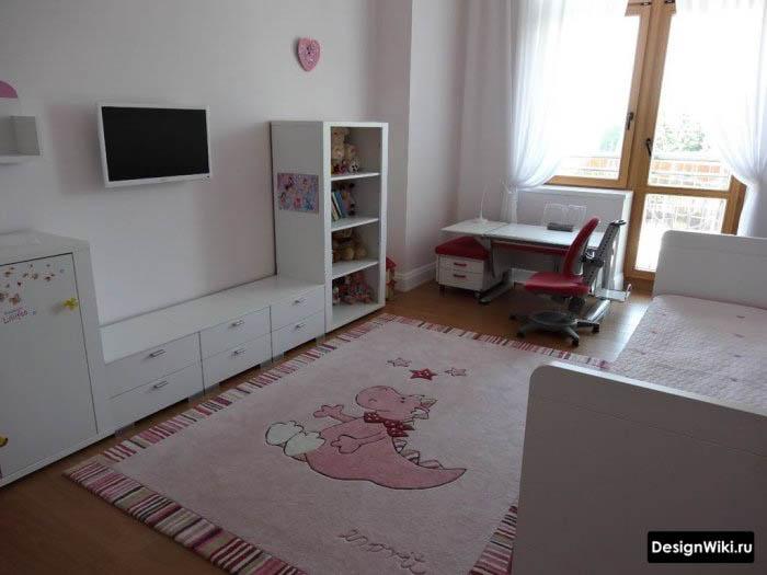 Белая мебель и розовый ковер в детской комнате