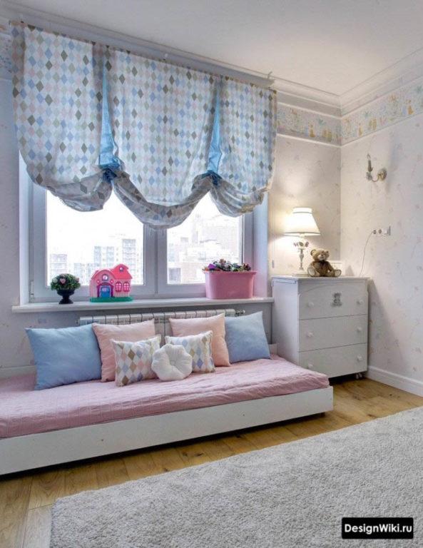 Кровать на полу возле окна в детской