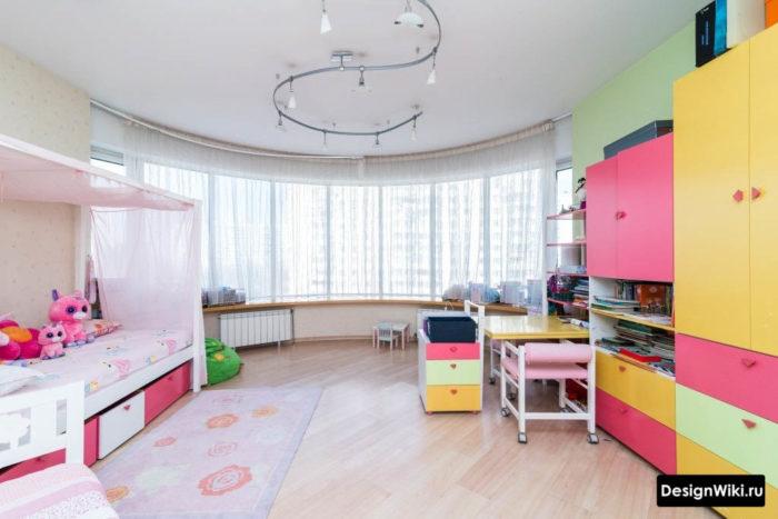 Простая отделка и яркая мебель в большой детской комнате