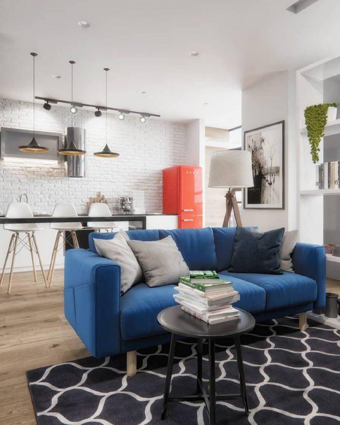 акцентный синий диван в современной скандинавской квартире студии