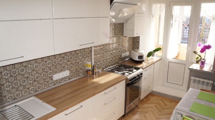 Белая кухня деревянная столешница узор на фартуке