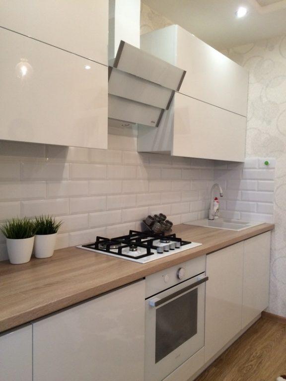 Белая техника на белой кухне с деревянной столешницей