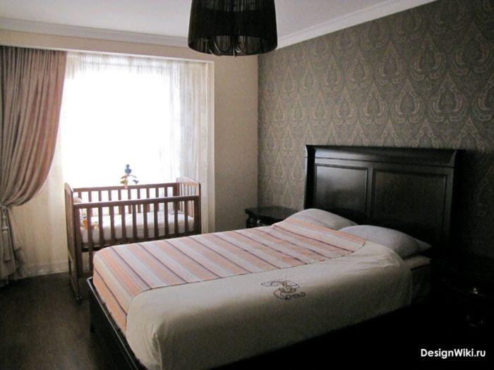 Детская кроватка возле окна в спальне