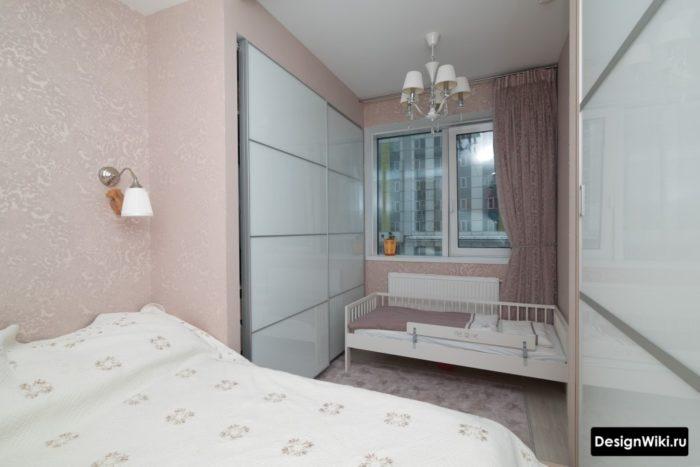 Детская кровать возле окна в спальне