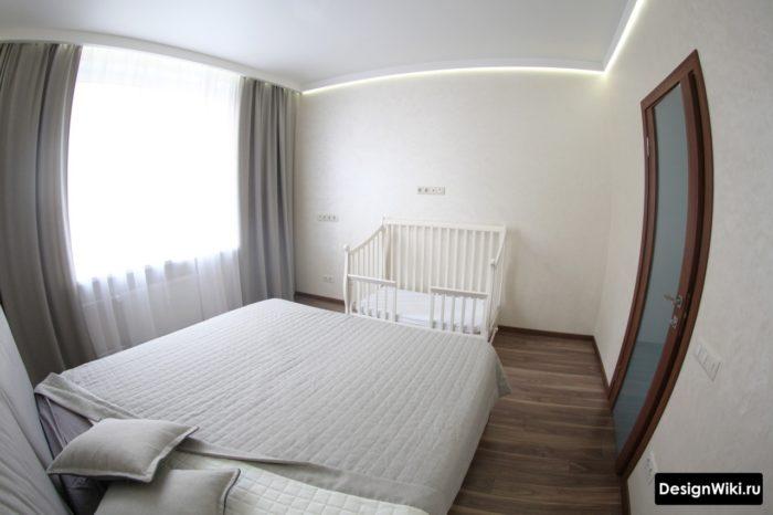 Спальня с детской кроваткой в ногах