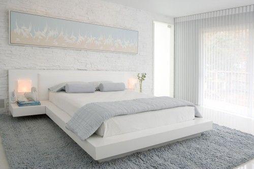 Белые стены и кирпичная кладка в спальне