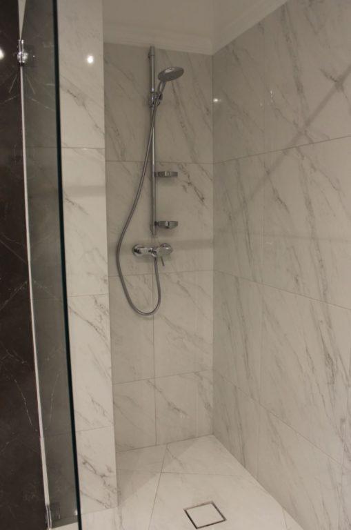 Душевая выложенная плиткой под мрамор
