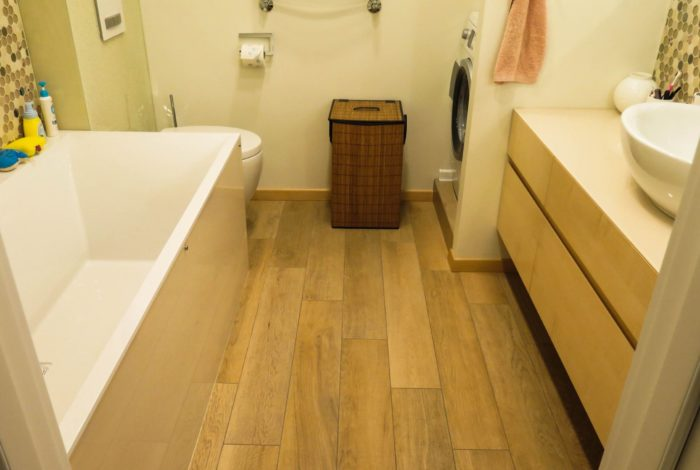 Коричневая плитка под дерево на полу ванной