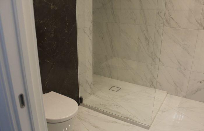 Крупная плитка под мрамор в совмещённой ванной