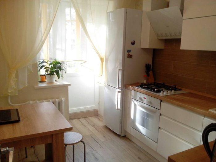 Маленькая кухня с белым гарнитуром и столешницей под дерево