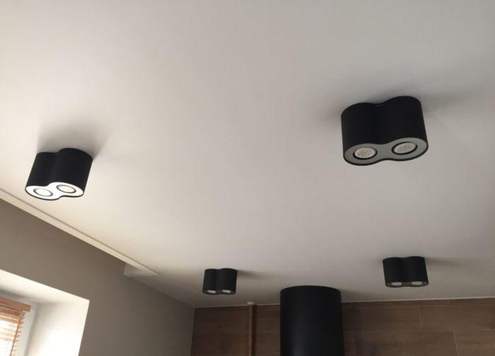Матовый белый потолок с чёрными цилиндрами светильниками