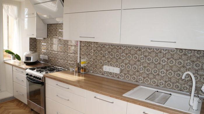 Маленькая белая кухня с узором на фартуке