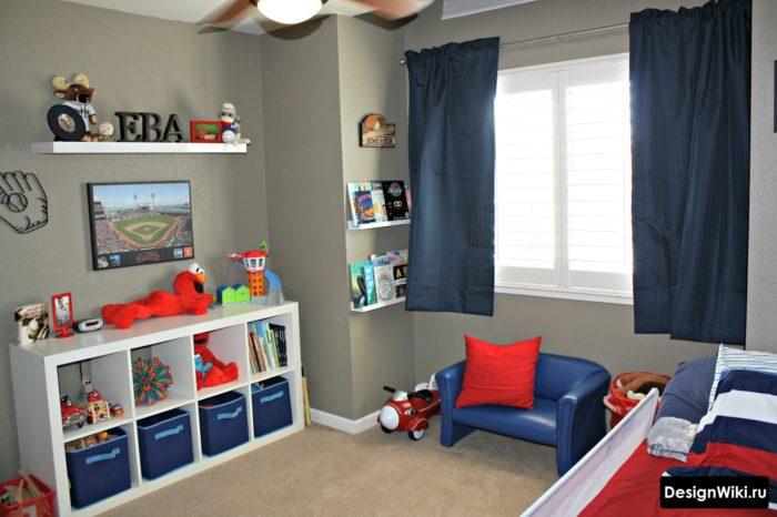 Серые обои, белые полки и синие шторы в комнате для мальчиков