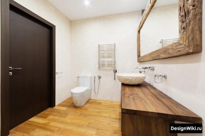 Оправа зеркала и тумба из дерева в ванной комнате