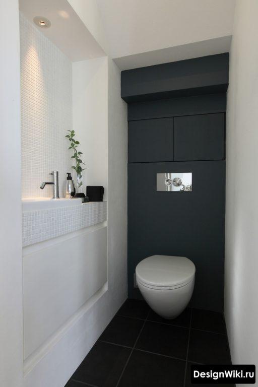 Светлые боковые стены и тёмная за унитазом в туалете