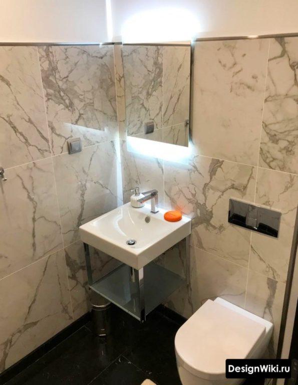Туалет с плиткой под мрамор до середины стены