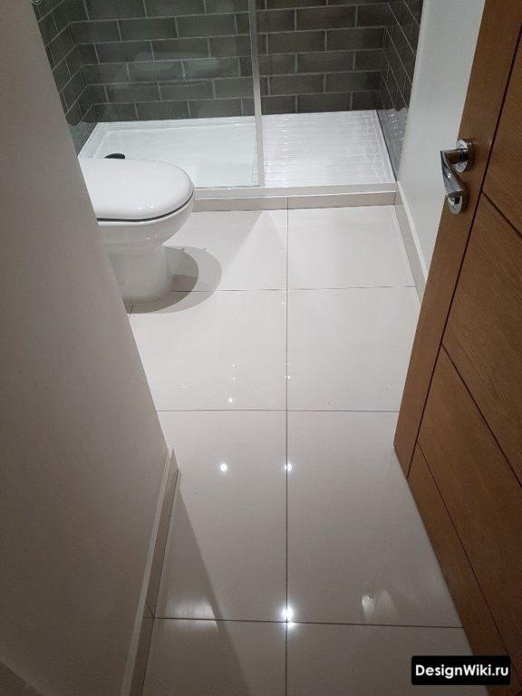 Белая глянцевая квадратная плитка 60 на 60 на полу ванной