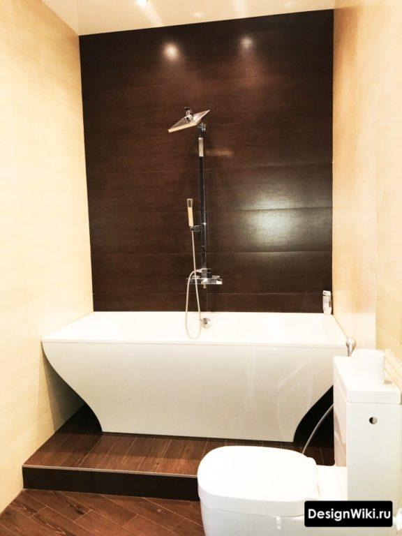Отделка черной плиткой стены за ванной