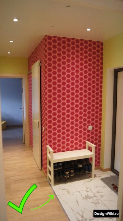 Алюминиевый порожек на стыке между плиткой и ламинатом в коридоре