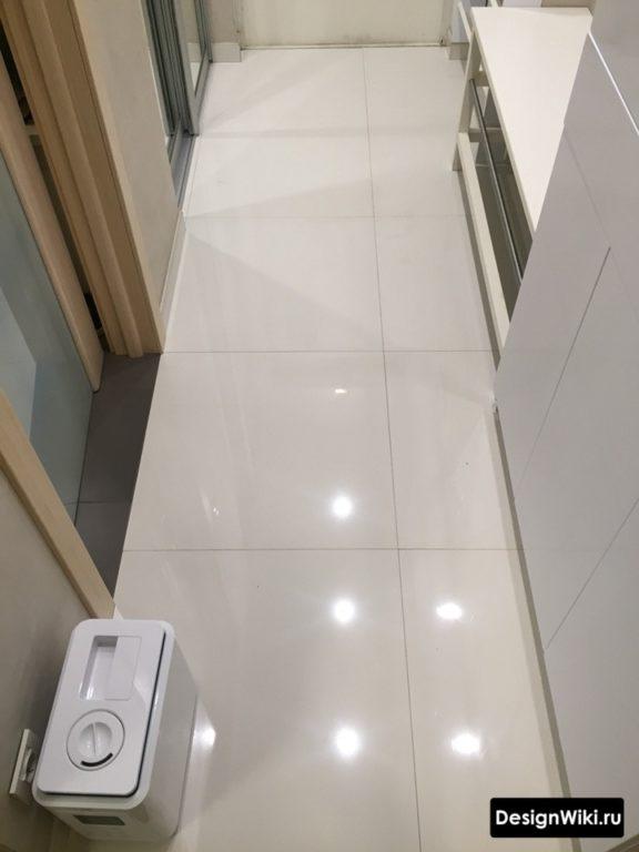 Белая глянцевая квадратная плитка на полу в коридоре