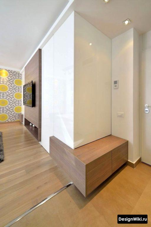 Белый глянцевый шкаф с сиденьем в небольшом коридоре