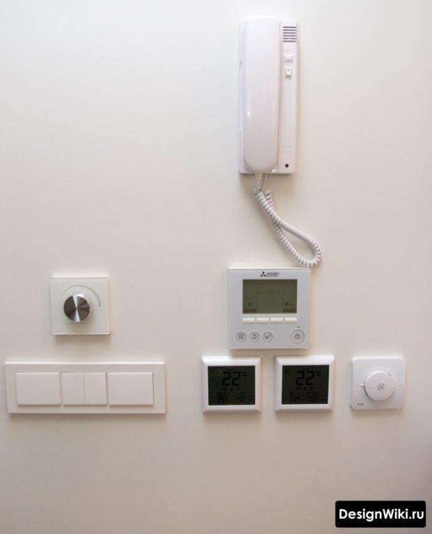 Блок с выключателями и домофоном на стене в маленькой прихожей