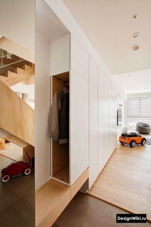 Изготовленный на заказ белый узкий шкаф в коридоре
