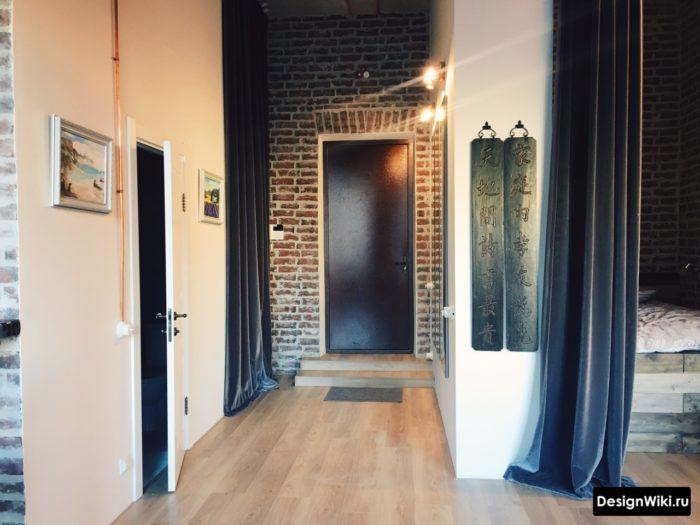 Красный кирпич на стене со входной дверью
