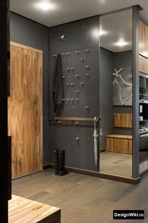 Открытые вешалки для верхней одежды на дверце шкафа прихожей в маленьком коридоре