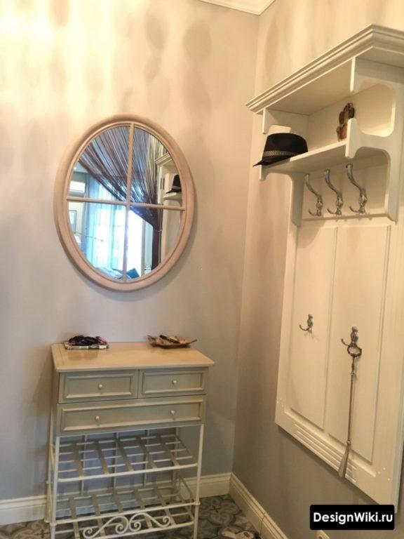Открытые вешалки, полки для обуви и овальное зеркало в мини-прихожей
