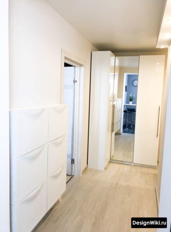 Угловой шкаф с зеркальной дверцей и узкая обвуница в маленьком коридоре