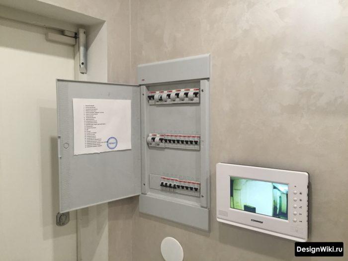 Щиток с автоматами и видеодомофон на стене в прихожей