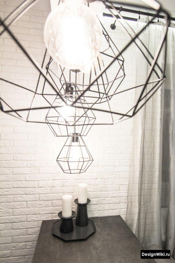 Проволочные светильники над барной стойкой между кухней и гостиной