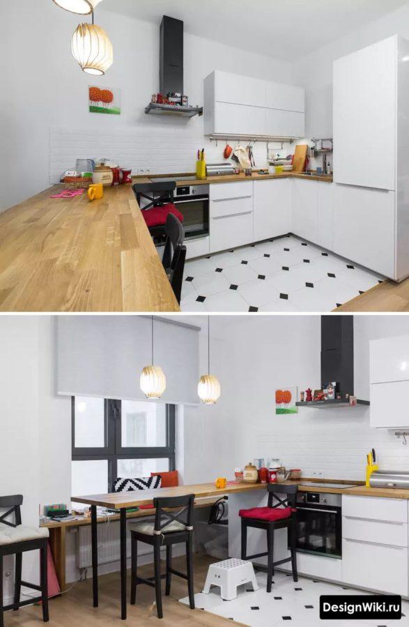 П-образная белая кухня с деревянной барной стойкой у окна