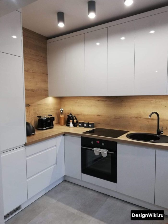 Белая глянцевая кухня в современном стиле с деревянной столешницей и фартуком