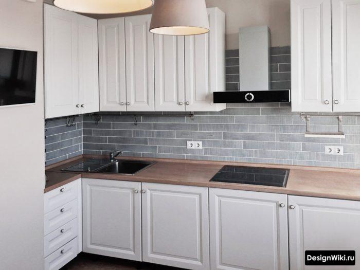 Белая кухня в стиле современная классика с деревянной столешницей и серым фартуком