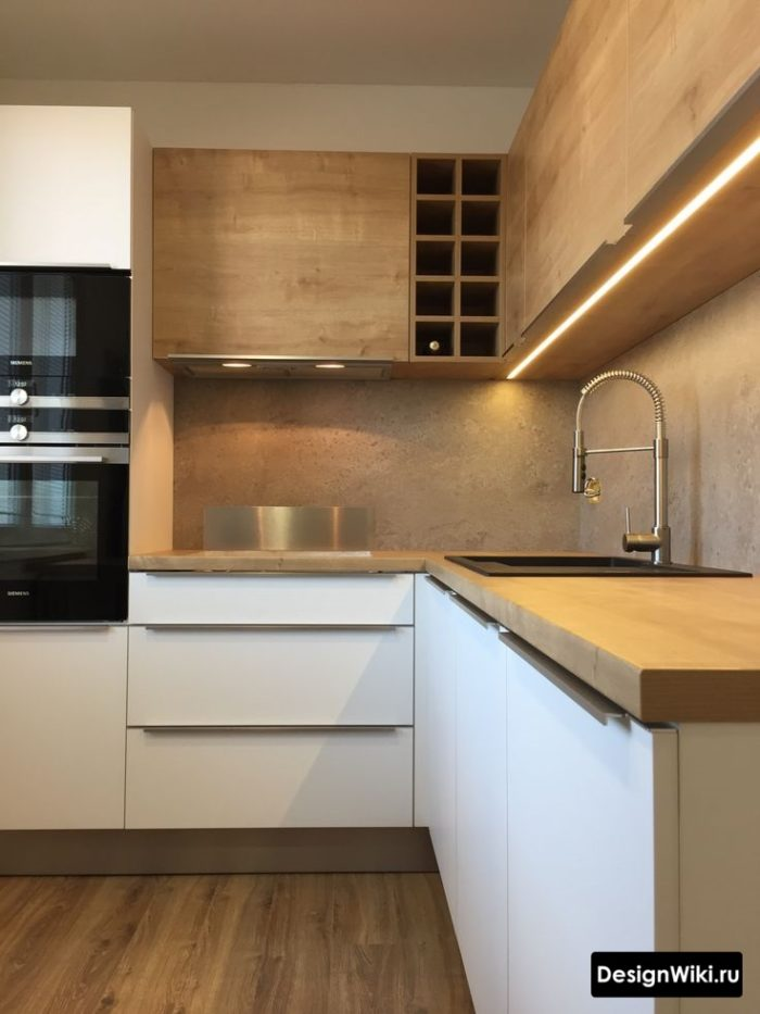 Белая кухня с деревянной столешницей и фартуком из бетона