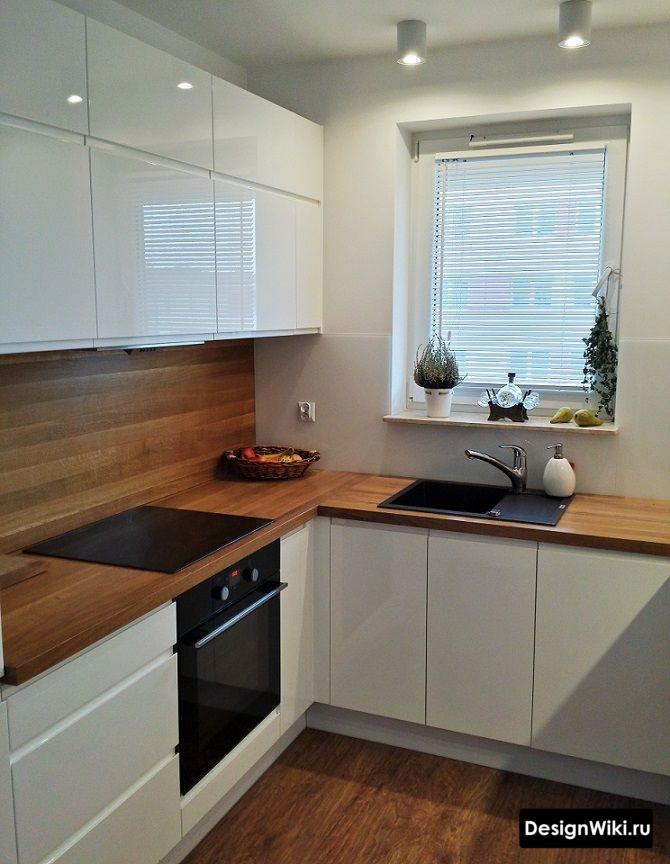 Белая кухня с деревянной столешницей и фартуком