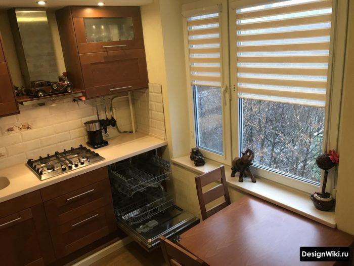 Встроенная в кухонный гарнитур посудомойка возле стены