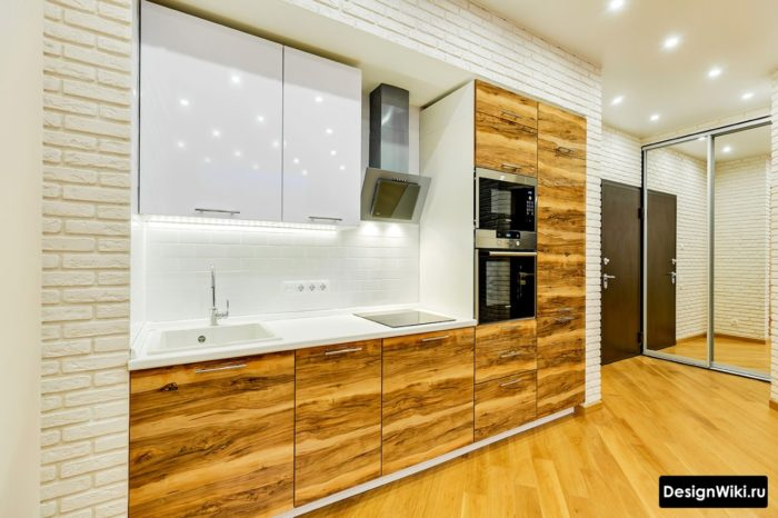 Встроенная кухня со шпонированными деревянными фасадами и белым глянцевым верхом
