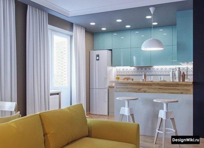 Голубые шкафы и желтый диван в кухне-гостиной с барной стойкой