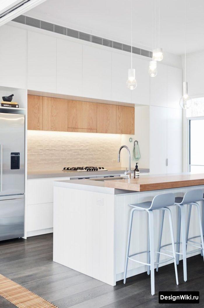 Дизайн белой кухни с островом и деревянными вставками