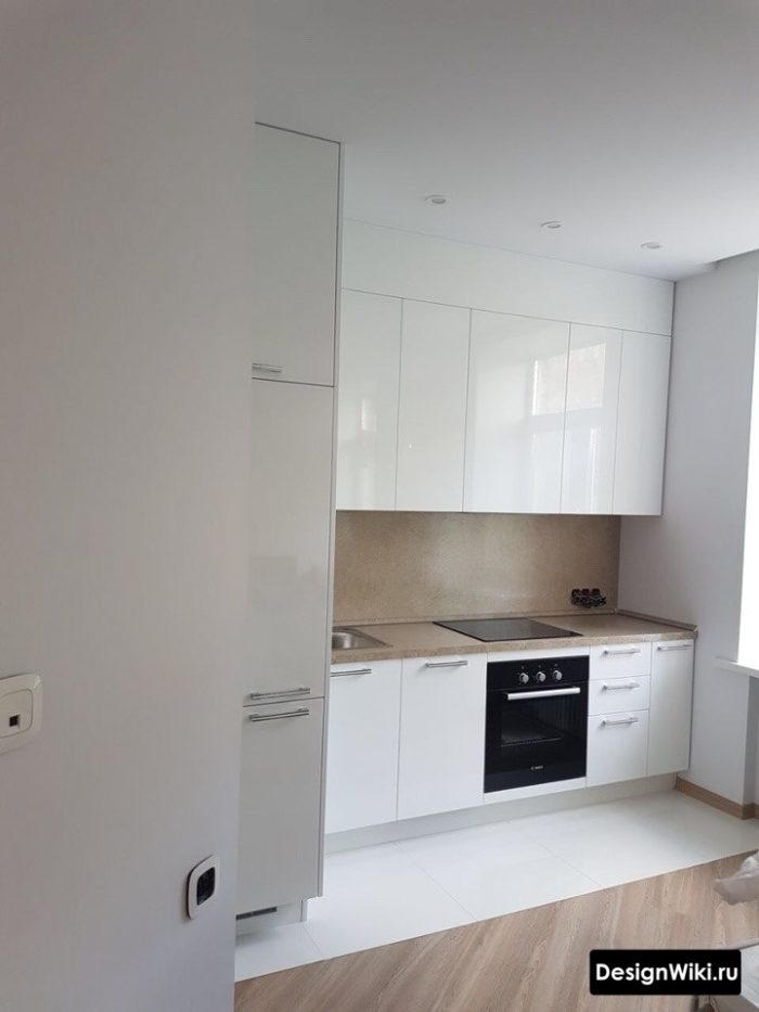 Зона из белой плитки на полу кухни и переход на паркет