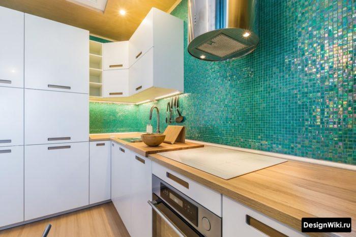 Интерьер белой кухни с деревянной столешницей и зеленым фартуком из мозаики