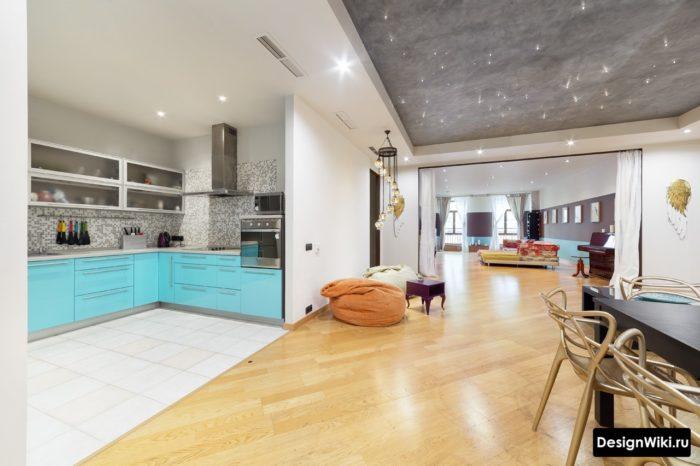 Кухня без двери с плиткой на полу и соседняя комната с ламинатом