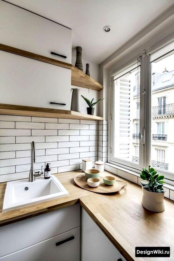 Кухня с белыми шкафами и фартуком и деревянной столешницей