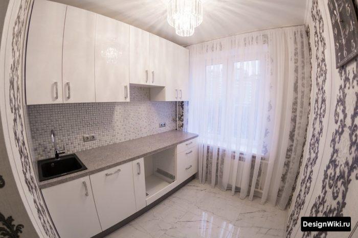 Прямой гарнитур в линию белого цвета на маленькой кухне
