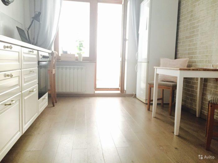 Светлый ламинат с фаской на полу кухни