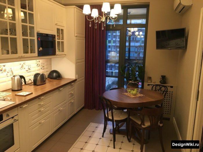 Темно-коричневая деревянная столешница в белой кухне в классическом стиле