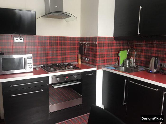 Черный кухонный гарнитур с красным фартуком